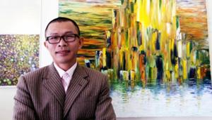 Họa sĩ Võ Trịnh Biện bên tác phẩm của mình.