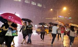 Người dân tại Đài Bắc, Đài Loan (Trung Quốc) đang đi bộ dưới cơn mưa lớn do siêu bão Soudelor gây ra. (Ảnh: EPA)
