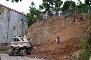 Đơn vị thi công tiến hành san ủi mặt bằng để đào móng, đổ bê tông kè tại khu vực bị sạt lở.