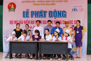 Ban đại diện cha mẹ học sinh, ban giám hiệu và các em học sinh trường THCS Sông Đà ký kết đội mũ bảo hiểm khi tham gia giao thông.