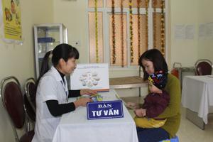 Cán bộ Trung tâm CSSKSS tỉnh tư vấn cho bà mẹ về lợi ích từ nuôi con bằng sữa mẹ. ảnh: P.V