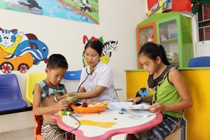 Cán bộ trạm y tế xã Tây Phong (Cao Phong) chữa bệnh cho trẻ em tại phòng khám thân thiện.