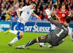 Tiền vệ Adam Johnson (áo trắng, tuyển Anh) trong pha đối mặt với thủ môn Diego Benaglio của Thụy Sĩ