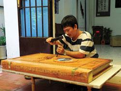 Nghệ nhân Trần Quốc Ẩn đang khắc bìa cuốn sách Hoa Lư thi tập .