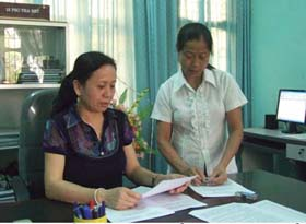 Chị Bùi Thị Xiềm (bên trái) trao đổi nghiệp vụ kiểm tra, giám sát với đồng nghiệp.