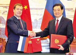 Tổng thống Nga Dmitry Medvedev (trái) và Chủ tịch Trung Quốc Hồ Cẩm Đào trao đổi các văn kiện hợp tác đã ký