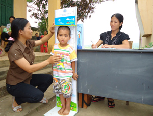 Nhân viên y tế thôn, bản xã Thanh Hối (Tân Lạc) theo dõi chiều cao của trẻ.