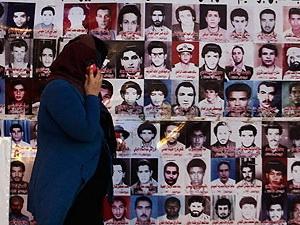 Một phụ nữ đi ngang qua những bức ảnh các nạn nhân bị thảm sát tại nhà tù Abu Salim.