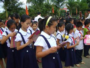 Trẻ em xã Mãn Đức (Tân Lạc) tìm hiểu về quyền trẻ em từ tài liệu, tờ rơi do Sở LĐ-TB&XH cung cấp.