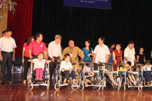 Đồng chí Trần Đăng Ninh, Phó Chủ tịch UBND tỉnh; lãnh đạo các sở, ban ngành tỉnh, thành phố và T.S Thích Giải Hiền, Hội trưởng Hội sự nghiệp từ thiện Minh Đức trao xe lăn cho trẻ em khuyết tật.
