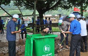 Lãnh đạo các sở, ngành tham gia dọn rác thải tại khu vực trước sân vận động huyện.