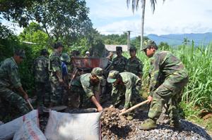 Lực lượng DBĐV huyện Tân Lạc gắn công tác huấn luyện với giúp nhân dân xóm Đon, xã Mỹ Hòa làm đường giao thông nông thôn.