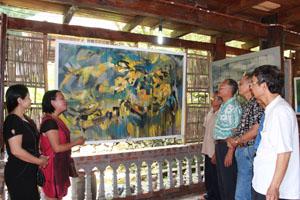 """Tác giả Trần Thị Thu, giải thưởng Hội Mỹ thuật Việt Nam đang chia sẻ với khách tham quan về tác phẩm sơn dầu """"Tôi"""", được trưng bày tại triển lãm mỹ thuật Hoà Bình năm 2014."""