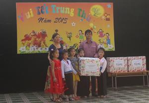 Đại diện huyện Tân Lạc trao quà cho trẻ em tại xã Đông Lai.